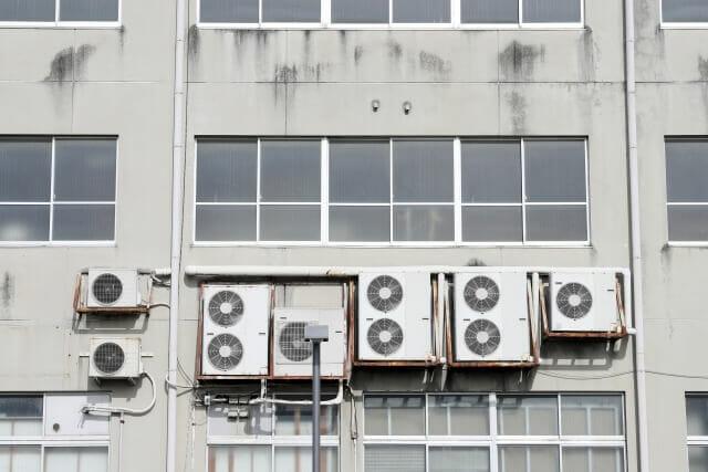 ビルで紫外線と雨風にさらされているエアコンの室外機